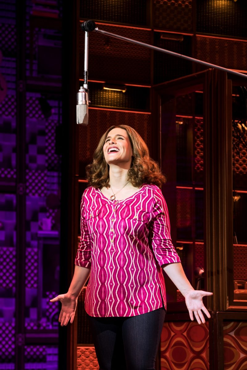"""The actress playing Carole King performing """"Natural Woman"""" at the mic in the recording studio"""