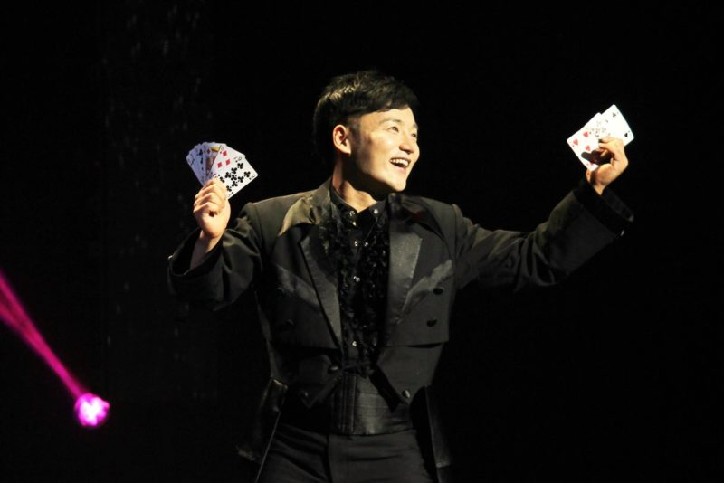 """An Ha Lim, also known as """"The Manipulator"""" stands on stage with cards fanned out in both hands, getting ready for his magic trick."""