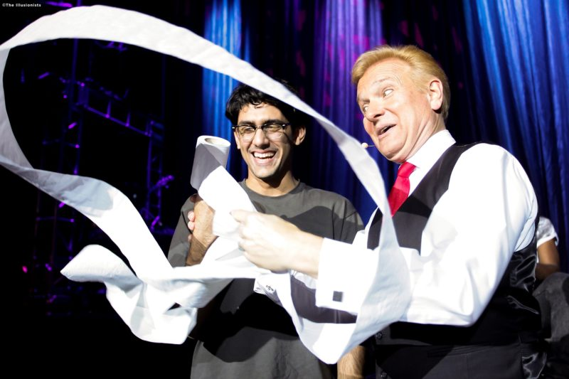 """Magician Jeff Hobson, also known as """"The Trickster"""" begins his famous paper trick by swirling a toilet paper roll around. An audience member standing by watches with a big grin on his face."""