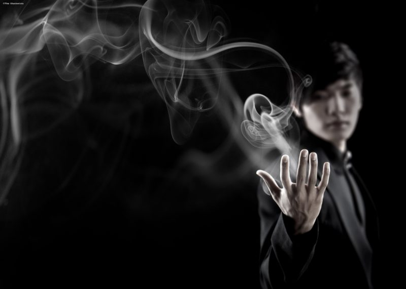 """The magician known as """"The Manipulator"""" extends his open hand. Smoke billows from his open palm."""