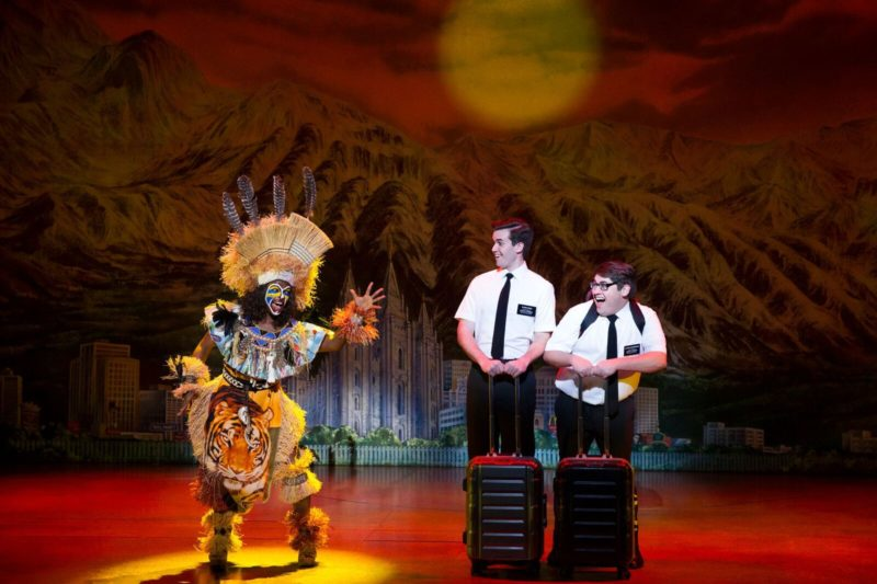 Two Mormons watch a woman dressed in over-the-top traditional African dressing. The woman looks like Rafiki from The Lion King